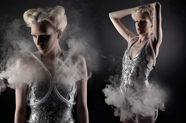 """'Smoke Dress' 2012 - is a  collaboration between fashion designer Anouk Wipprecht and technologist Aduen Darriba. The dress is a tangible couture """"smoke screen imbued with the ability to suddenly visually obliterate itself through the excretion of a cloud of smoke. Ambient clouds of smoke are created when the dress detects a visitor approaching, thus camouflaging itself within its own materiality."""