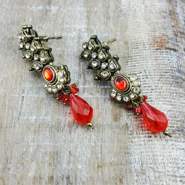 Ikao - Play up your outfit in these antique gold earrings with red and clear cubic zirconium stones to help it all shine together.