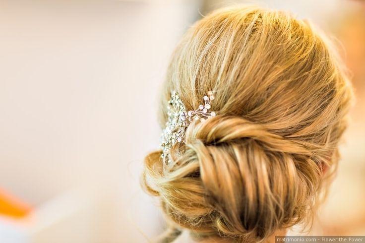 Acconciatura da sposa raccolta in uno chignon basso con un accessorio da sposa elegante