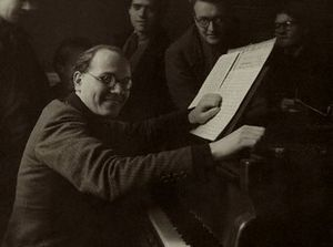 A middle-aged, balding man with swept back dark hair, wearing a dark suit, seated at an upright piano. He faces the camera, his left hand on an open musical score, his right hand resting on the side of the piano. Four people can be seen in the background.