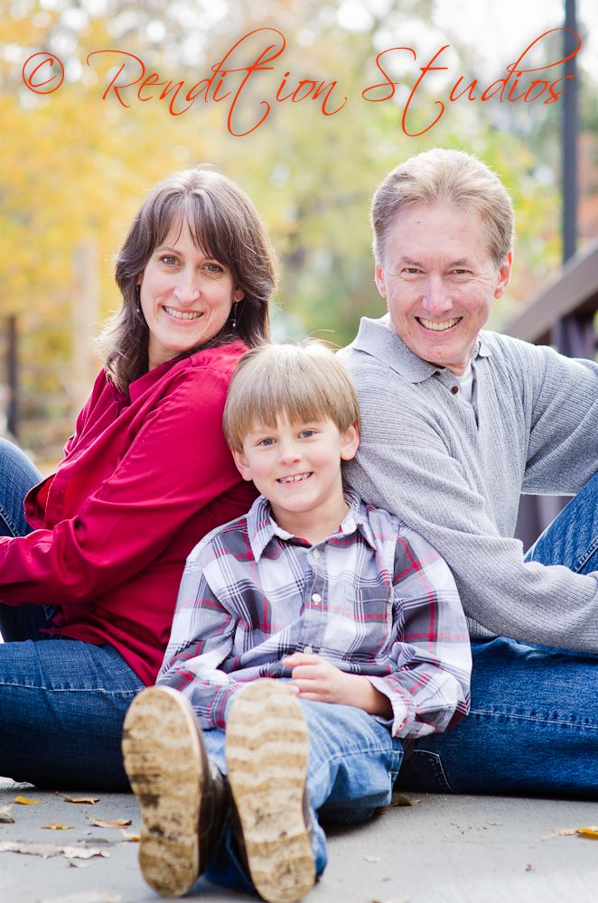 family of three on a bridge, outdoor session at the end of the fall season