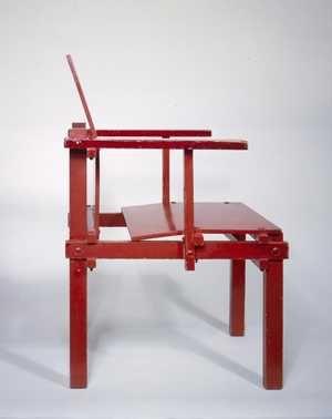Stoel met verende zitting | Gerrit Thomas Rietveld | 1925 | Centraal Museum Utrecht. Het frame van de stoel heeft dezelfde constructie als de militaire stoel. Rietveld heeft bij dit model armleuningen toegevoegd. De zitting en de rug zijn gemaakt van gebogen multiplex, waardoor een verende zitting ontstaat. Het comfort is bij deze stoel dan ook hoger dan bij de militaire stoel.