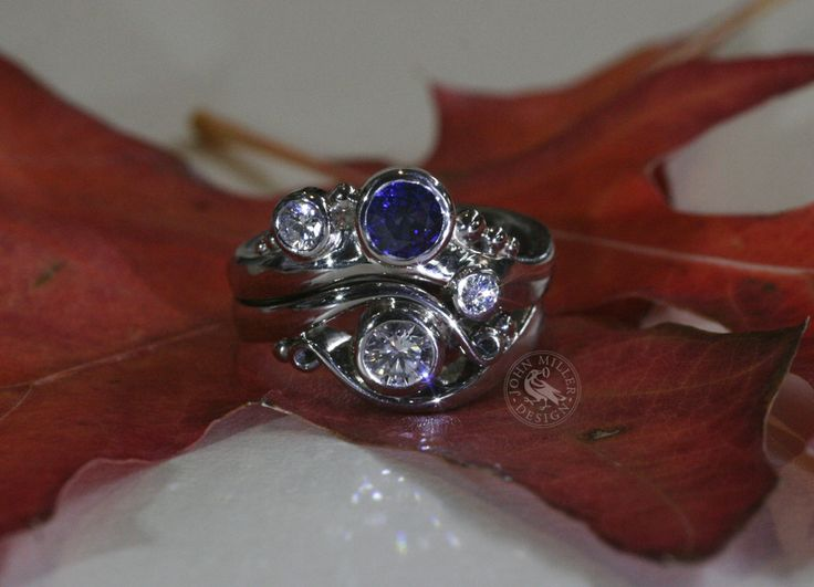 18ct White Gold ring set with a beautiful blue Ceylon sapphire and smaller diamonds, designed to sit snugly next to their previous John Miller Design diamond ring creation 'Brilliance'