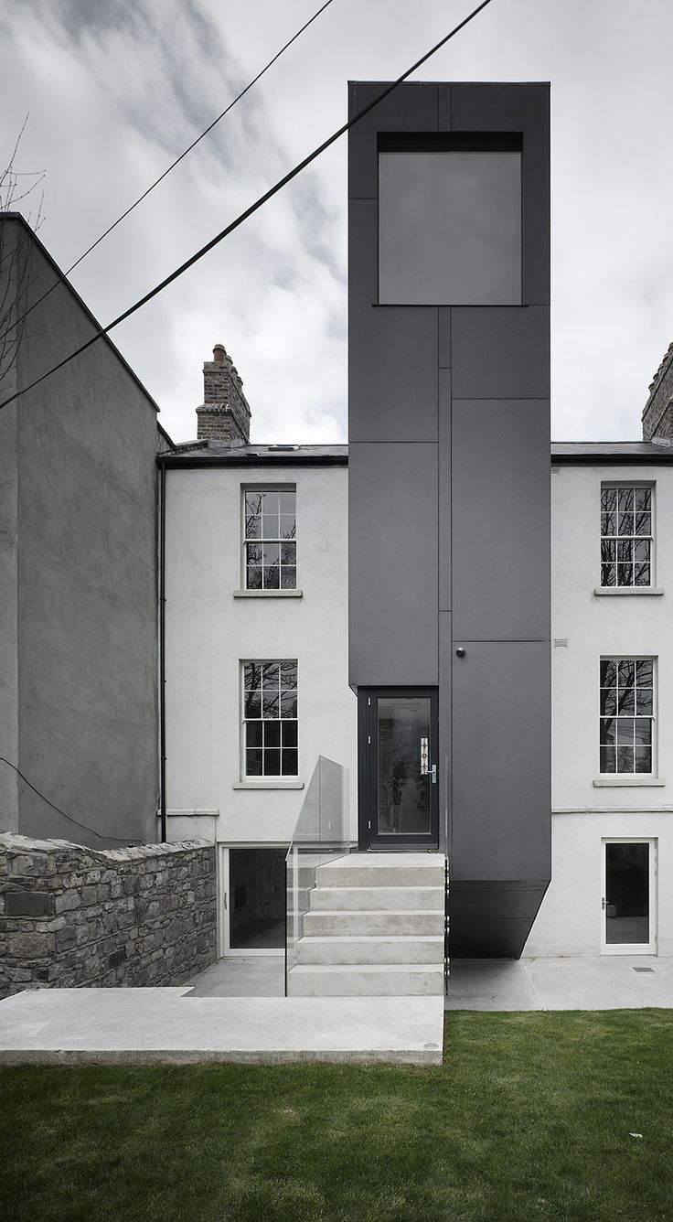ODOS Architects white open access/stairs to black volume, contrast rough stone wall vs smooth façade, small entrance big view, extreme proportions, asymmetry, verticality