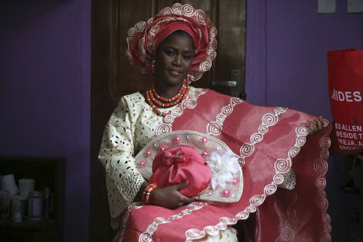 A Nigerian bride stands out in her brightly colored lace blouse and patterned kaftan, or robe, often made of imported Indian fabrics. Coral beads and a headdress complete the look.