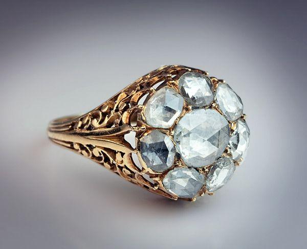 Antique Georgian Rose Cut Diamond Cluster Ring.  An elaborate openwork 18K gold ring, circa 1820, is set with eight antique rose cut diamonds.