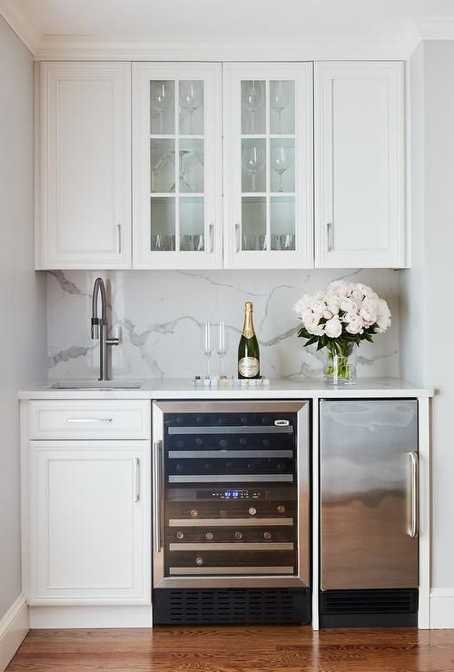 Beautiful white wet bar features glass front cabinets mounted between white raised panel cabinets fitted above a square sink with a satin nickel gooseneck faucet.