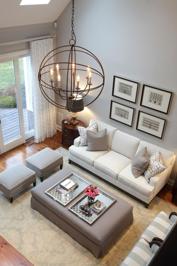 High Ceilings And Stylish Design This Living Room Uses A Beautiful Palette Of Soft Gray White An Orb Chandelier Black Framed Art