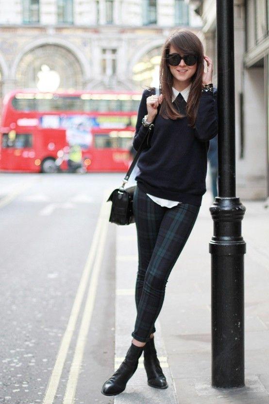 schwarzer Pullover mit einem Rundhalsausschnitt, weißes Businesshemd, dunkelblaue und grüne enge Hose mit Schottenmuster, schwarze Leder Stiefeletten für Damen