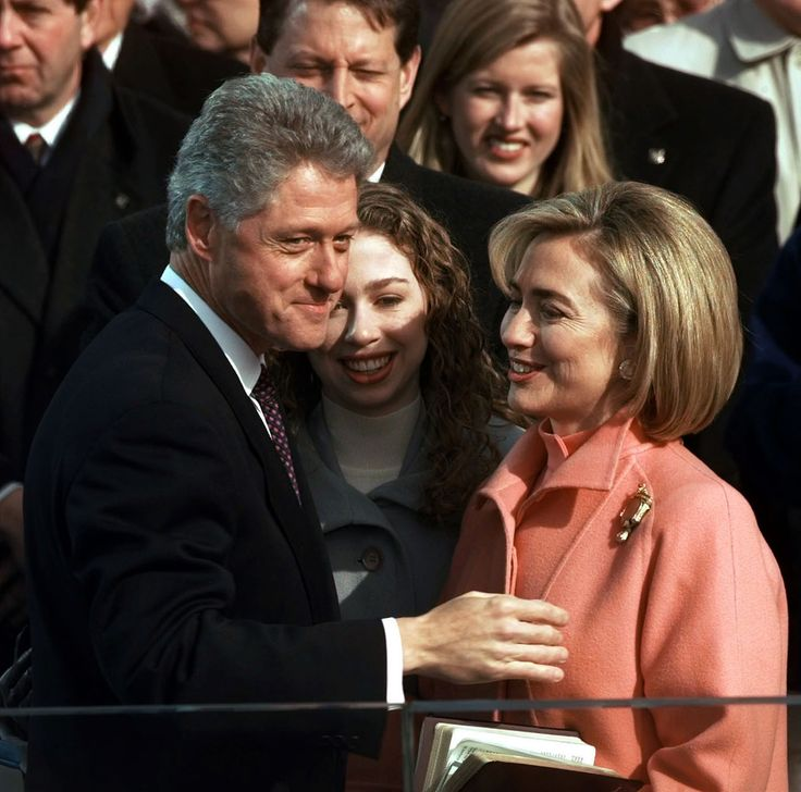 President Clinton, his daughter Chelsea and wife Hillary talk after Clinton was sworn in for his second term by Supreme Court Chief Justice William Rehnquist during the 53rd Presidential Inauguration on January 20, 1997. We love the salmon color that Hillary chose for her suit, and that daughter Chelsea was able to join them on stage.Photo Credit: Doug Mills, AP                            President Clinton, his daughter Chelsea and wife Hillary talk after Clinton was sworn in for his second…