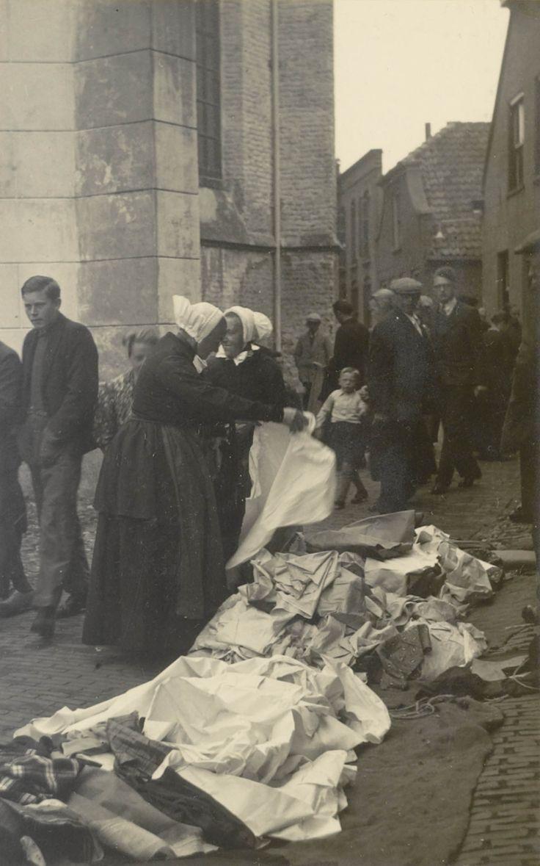Markt bij de grote kerk te Ommen. 1940 De twee vrouwen in streekdracht zijn gekleed in opknapdracht. De mannen en jongens dragen modekleding. #Overijssel #Salland #Saksen