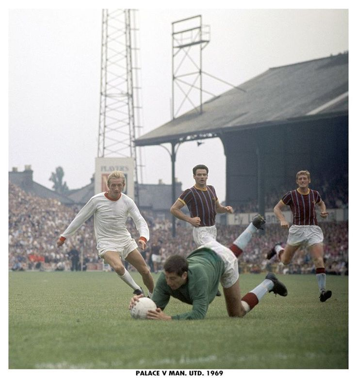 9th August 1969. Crystal Palace goalkeeper John Jackson dives at the feet of Manchester United forward Denis Law watched by team mates Roger Hynd and John McCormack.