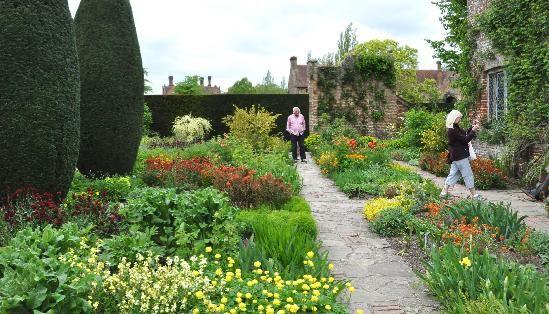 De Cottage Garden bruist van warme kleuren, zelfs op een regenachtige dag in mei, dit was een stukje tuin waar zowel Harold als Vita dagelijks op uitkeken, Harold vanuit zijn studeerkamer en Vita vanuit haar slaapkamer. Bemerk ook de 4 reusachtige Ierse taxus snoeivormen (Taxus baccata fastigiata)