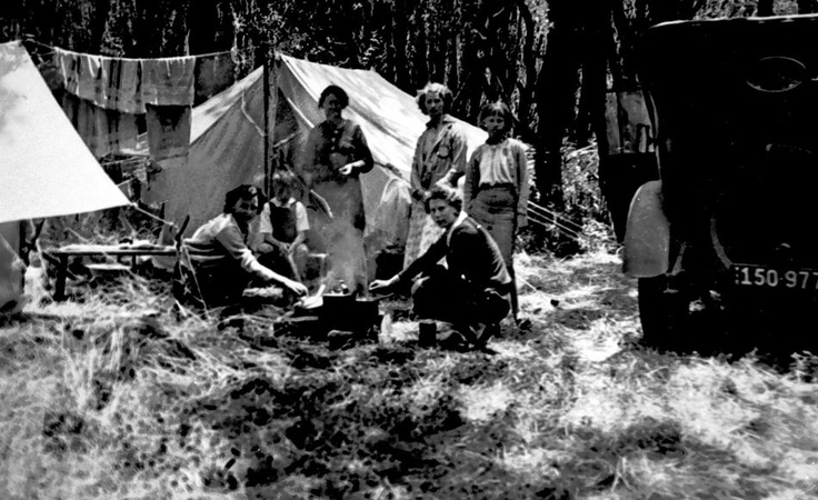 1936, camping on the foreshore at Rosebud,Victoria Australia They are grouped around a camp fire, there are tents on the left and a car on the righ