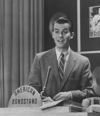 """Dick Clark, in the late 1950s, at his podium station for the popular TV dance show, """"American Bandstand."""""""
