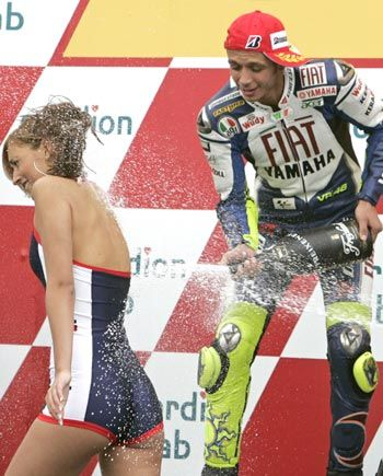 valentino rossi spraying some white fluid onto a lass