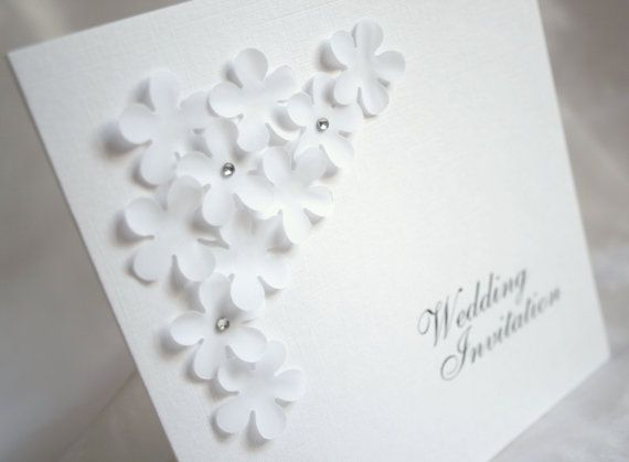 Wedding Invitation: Elegance. Handmade flowers cut from a beautiful, delicate stock are layered on this invitation give a romantic, tactile edge.
