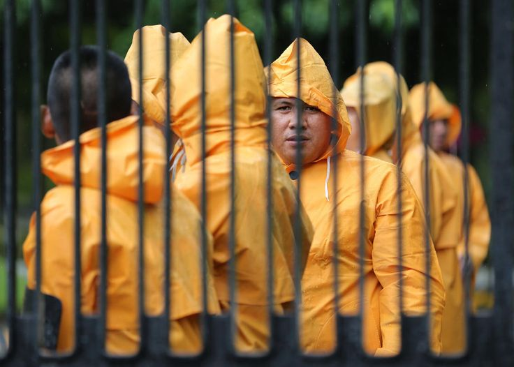 Filipino security guards wear raincoats as they keep watch at the Department of Foreign Affairs in suburban Pasay, Philippines on Tuesday Aug. 5, 2014. Philippine weather forecasters say Typhoon Halong has worsened monsoon rains, flooding northern villages, but is too far off at sea to hit the country as it continues to blow toward southern Japan.