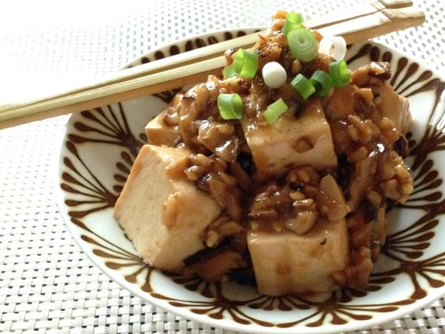 肉なし簡単!麻婆豆腐 木綿豆腐1丁 干ししいたけ3枚 にんにく(みじん切り) 1かけ しょうが(みじん切り) 大さじ1 オリーブオイル大さじ2 片栗粉(同量の水で溶く)大さじ1 しょうゆ大さじ1 青ねぎ(小口切り)適量 七味とうがらし適量 豆腐は水切りする。干ししいたけはぬるま湯に浸して戻す。干し椎茸は水気をしぼってみじん切りにする。豆腐は一口大に切る。鍋ににんにくとしょうが、オリーブオイルを入れて弱火にかける。にんにくの香りがしてきたら干し椎茸を加えて炒め、水溶き片栗粉を回し入れる。木べらで混ぜてしょうゆを加える。温まったら豆腐を加えて崩れないように混ぜ、全体が温まるまで火を入れる。器に盛り、青ねぎをちらし、七味とうがらしをふる。