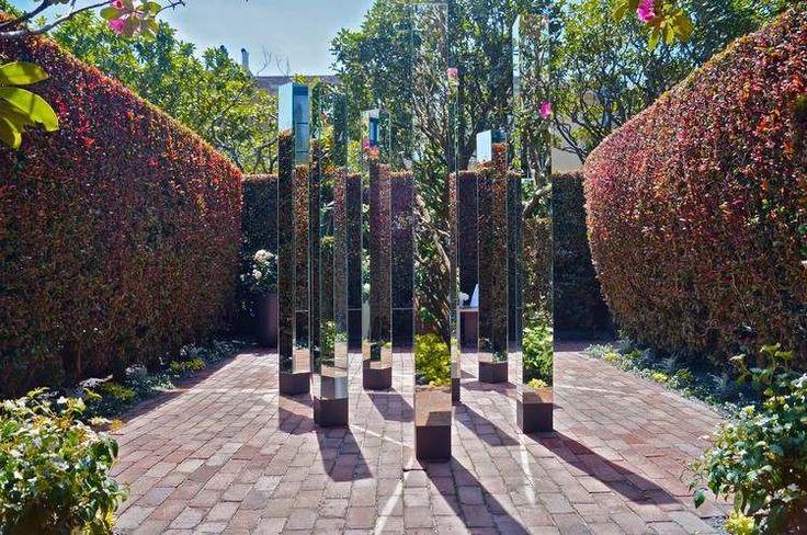 sculptures contemporaines recouvertes de miroirs, sol en pavés rouges et haie verte