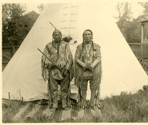 Chippewa Chief Big Rock, holding a pipe; standing with Crazy Boy, Great Falls, Montana.