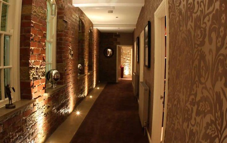 Brick hallway with uplighting and stuff in windows.
