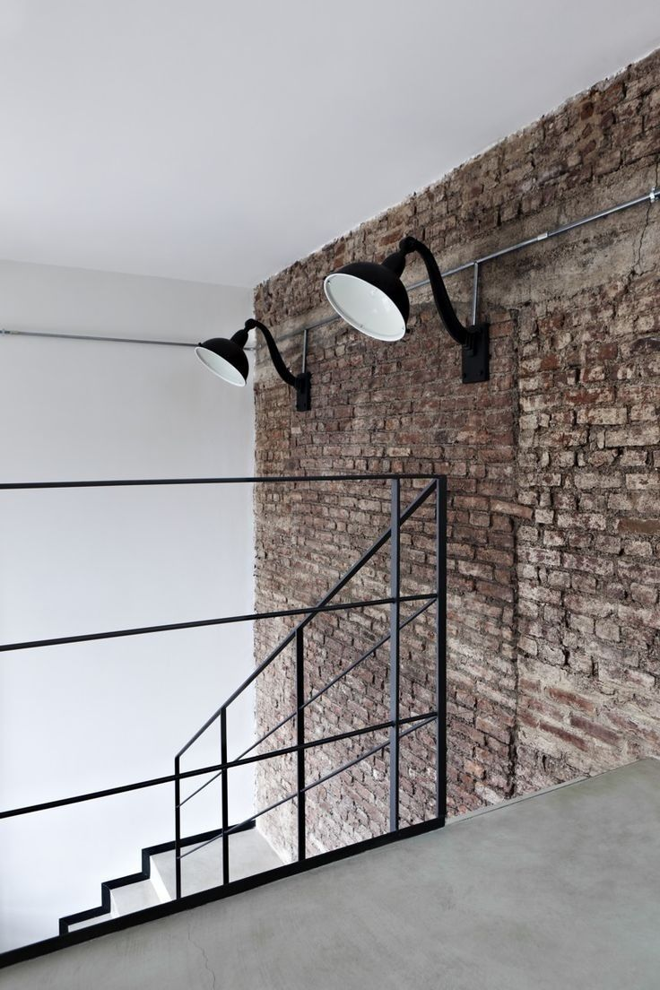 polished concrete floor, exposed brick wall, simple railing - contrast