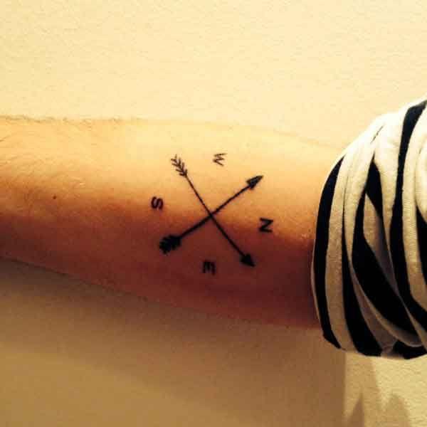 Tatuaje de una brújula formado por dos flechas entrecruzadas en el antebrazo de Marcel.