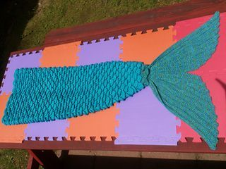 Mermaid Lap Blanket made in two parts: body and tail and then joined. Made with crocodile stitches for the appearance of scales and the tail is ribbed. Adult, teen and child sizes. Due to the nature of the stitch the gauge is not an exact science. Cocoons around feet and ankles and then opens as blanket.