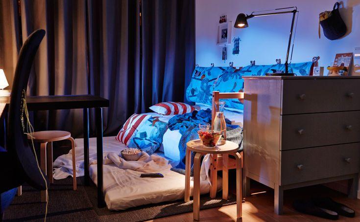 Ein Wohnheimzimmer vorbereitet für einen Filmabend: Das MERETE Gardinenpaar in Grau ist zugezogen, eine Matratze liegt zur Sitzfläche umfunktioniert auf dem Boden.