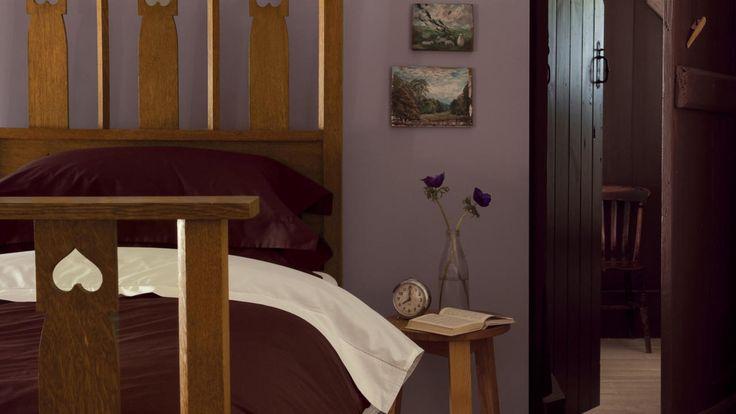 Paredes roxas trazem conforto e nostalgia para este quarto aconchegante.