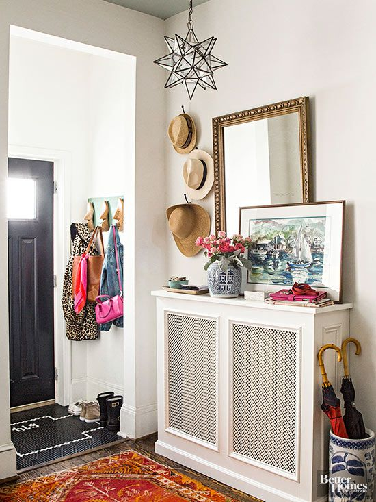 A radiator doesn't have to be that creaky old thing you try to ignore. Cover one with vented woodwork, then spruce it up with vases, artwork, and practical hooks. A pretty glass pendant further showcases the often overlooked space./