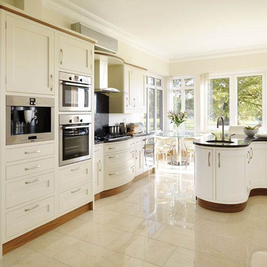 Kitchens: Cream Kitchen with Curved Island also Sleek Dark Worktop plus White Microwave Cabinet and Three Holes Sink Faucet