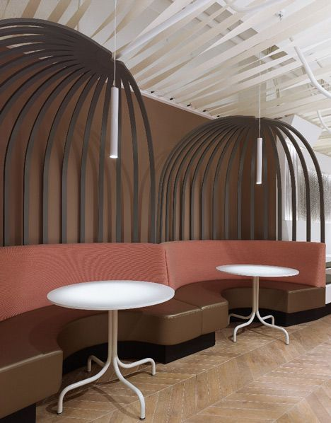 Vertical strips rise from the back of circular booths and curve at ceiling height to look like oversized birdcages.