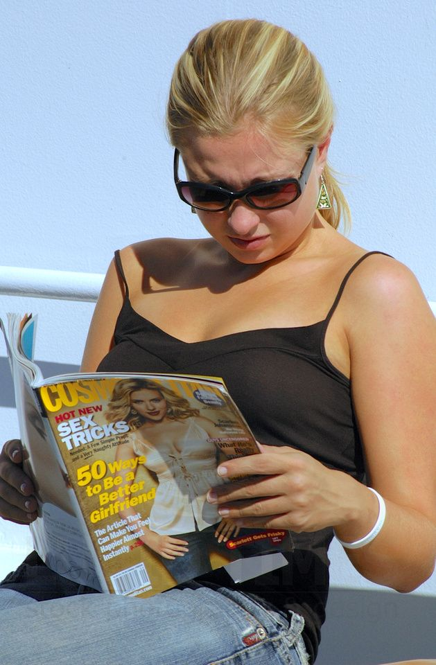 Beautiful blonde travelling with Cosmopolitan fashion magazine