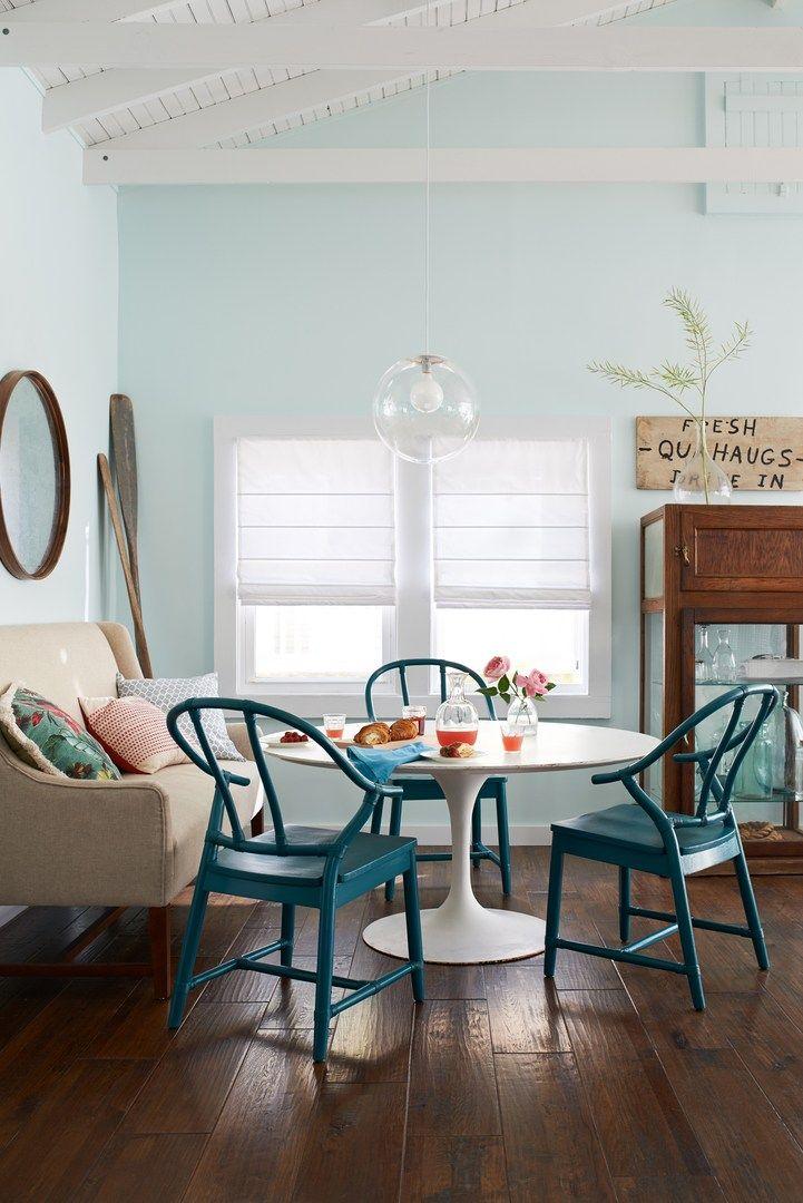 funky cabin dining room, dark wide plank floors, light blue walls, settee, mid century table, turquoise