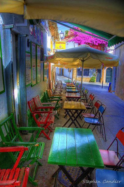 Cádiz (Andalucía) - Contrasting colourful tables and chairs in a cafe, Conil de la Frontera