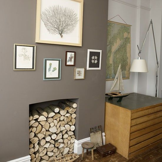 The chimney breast is painted in an earthy shade of brown and the fireplace filled with logs to add a touch of drama to the living room.