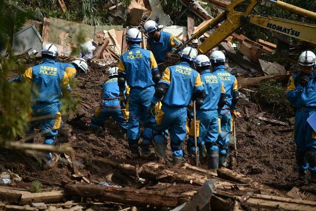 倒壊した建物跡で捜索を行う警察官=熊本県南阿蘇村