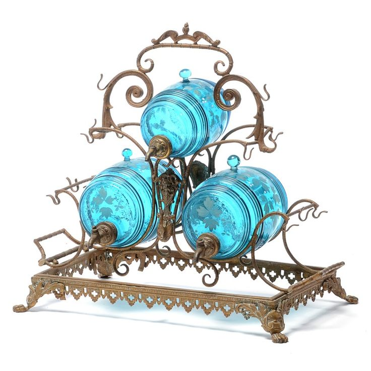 A late Victorian liquor dispenser on cast brass stand. There are three barrel dispensers of blown glass in sapphire blue, each with hand-painted leaf borders and brass spigots. Each dispenser has a glass stopper and is mounted on a scrolled wire framework with a center handle and hooks. The piece was made circa late 19th century.