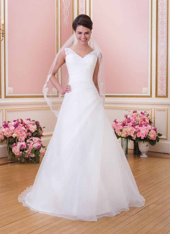 Sweetheart Gowns sweetheart style 6024 Organza asymmetrical draped A-line features sheer lace V- tank neckline.  Style has chapel length train and organza buttons over zipper.