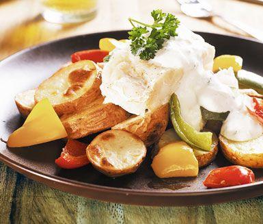 Ugnsbakad fisk med vitlökssås - Portioner:  4 handle 12 potatisar 2 msk olivolja 2 tsk salt 3 paprikor (gärna i olika färger) 600 g torsk- eller hokifilé 1 krm peppar Sås 2 dl matyoghurt 3 vitlöksklyftor 2 krm salt 1 krm peppar 3 msk hackad persilja eller dill