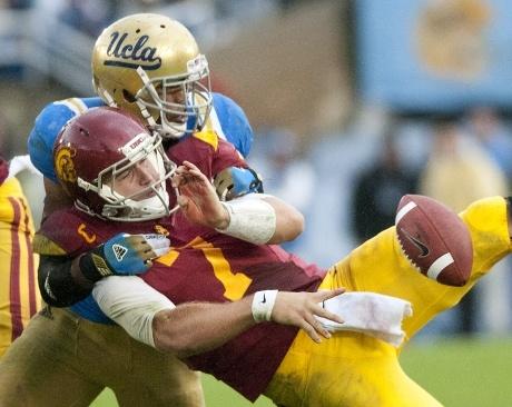 Anthony Barr rips down Trojan senior quarterback Matt Barkley in the fourth quarter.