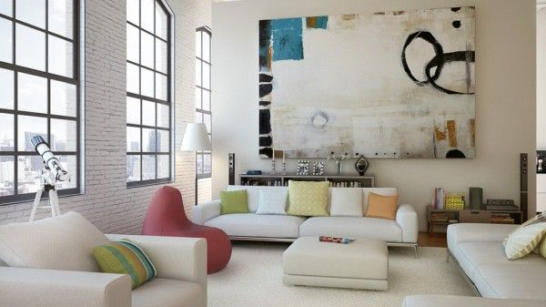 This modern loft living room uses light colors to reflect and call attention to the sunlight that is allowed to stream through the massive windows. Small pops of color add warmth without being too edgy.