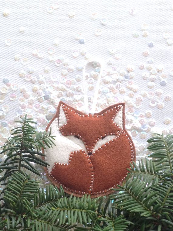 Although foxes do not hibernate in winter, this charming felt critter will gladly take a nap on your tree. The first one in the Sleepy Pals series, this fox is hand-cut and appliqued layer by layer using hand-guided machine stitch. The eyes and nose are hand-embroidered. ITEM DESCRIPTION: - 100% merino wool felt (Oeko-Tex Standard 100 certified*), and/or 100% wool felt - Measures appr. 3 1/2 in diameter - 2 1/2 satin ribbon hanging loop - Lightweight, no stuffing, layered felt applique…