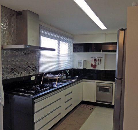 Se a cozinha tiver uma largura um pouco maior, dá para prolongar a bancada em L e usar a parede mais curta para instalar o forno. Neste projeto de Karina Correa, o filtro e um suporte para utensílios de cozinha também ocupam o espaço.
