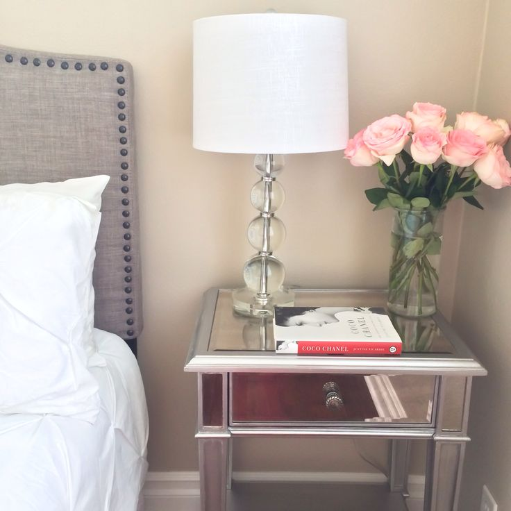 Master bedroom- gray headboard, white tufted comforter set, glass lamp, mirrored nightstand and pink roses