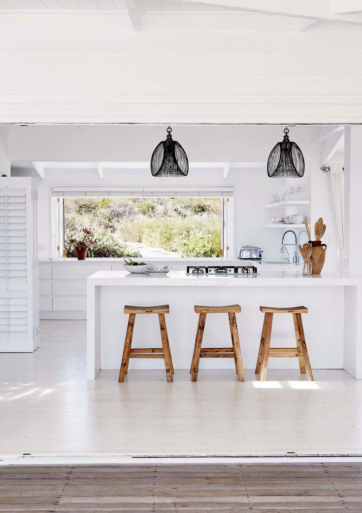 La barra pintada de blanco que separa la cocina del linving comedor de esta casa de playa en Sudáfrica tiene bancos 'Hylosi' (Weylandts), inspirados en los tradicionales asientos chinos.