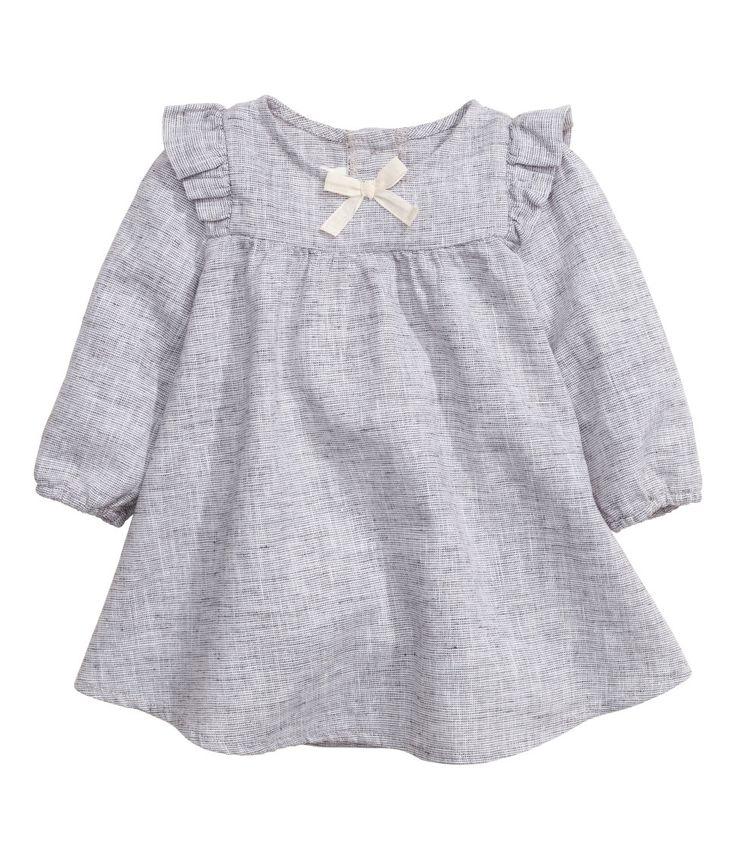 BABY EXCLUSIVE. Een jurk van een gemêleerde, geweven linnen/katoenmix. De jurk heeft een volant op de schouders, een decoratief strikje voor, lange mouwen met elastiek onderaan en een sluiting in de nek.