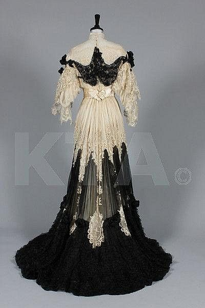 circa 1905 Ivory tapelace and black chiffon evening gown, the boned bodice trimmed with black satin rosettes to the shoulders and swags of sequined tulle edged in beaded pom-poms, deep pointed V to ivory satin waist, ruffles of lace to the sleeves, the separate skirt similarly trimmed and adorned. Back